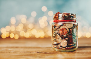 Donation money jar filled with coins in front of holiday lights